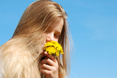 Beautiful girl with dandelions. Beautiful blonde girl holding a bunch of dandelions, clear sky in the background royalty free stock photo