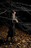 The beautiful girl in dark autumn wood Stock Image