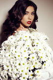Beautiful girl with dark hair with big bouquet of daisies Royalty Free Stock Images