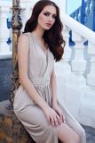 Beautiful girl with dark hair and blue eyes in elegant beige dress Royalty Free Stock Images