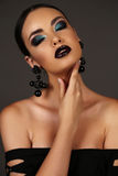 Beautiful girl with dark hair with bright extravagant makeup and bijou Stock Photography