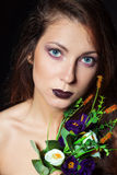 Beautiful girl with dark hair and bright make-up with a bouquet of purple flowers in the Studio on a black background. New years makeup, blue eyes Royalty Free Stock Photo