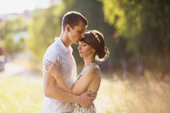 Loving couple in the forest on a sunny day. To love each other. Beautiful girl with dark hair and brown eyes with a wreath on head in summer dress hugging a men Royalty Free Stock Photography