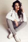 Beautiful girl with dark hair in casual clothes posing in studio Royalty Free Stock Photos