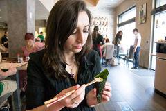 Beautiful girl with dark hair, dressed in black is holding chopsticks and temaki sushi Royalty Free Stock Image