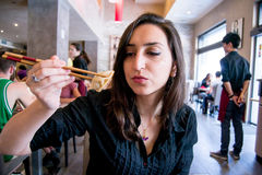 Beautiful girl with dark hair, dressed in black is holding meat ravioli with chopsticks Stock Images