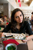 Beautiful girl with dark hair, dressed in black is holding a plate full of sushi Royalty Free Stock Photo
