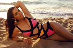 Beautiful girl with dark hair in elegant bright bikini posing on beach Stock Photos