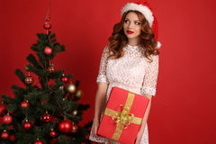 Beautiful girl with dark hair  in elegant dress with big Christmas present Royalty Free Stock Photo