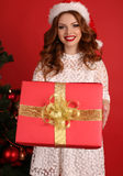 Beautiful girl with dark hair  in elegant dress with big Christmas present Royalty Free Stock Images