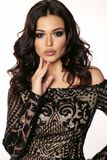 Beautiful girl with dark hair and evening makeup in luxurious bl. Fashion photo of beautiful girl with dark hair and evening makeup in luxurious black lace dress royalty free stock photos