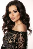 Beautiful girl with dark hair and evening makeup in luxurious bl. Fashion photo of beautiful girl with dark hair and evening makeup in luxurious black lace dress royalty free stock photography