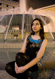 Beautiful girl with dark hair and eyes sitting near a fountain Stock Photo