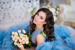 Beautiful girl with dark hair with flowers in her hands in a blu royalty free stock photos