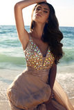 Beautiful girl with dark hair in luxurious dress posing on beach Stock Photos
