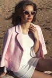 Beautiful girl with dark hair posing on beach Stock Image