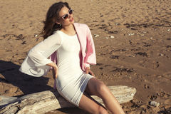 Beautiful girl with dark hair posing on beach Royalty Free Stock Images