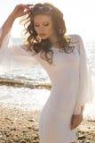 Beautiful girl with dark hair posing on beach Stock Images