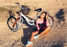 Beautiful girl with dark hair sitting beside a bicycle on beach Stock Photos
