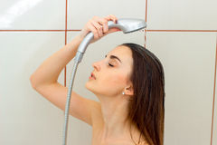 Beautiful girl with dark hair washes her head under the shower Stock Images