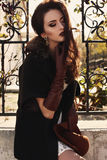 Beautiful girl with dark hair wearing elegant coat and leather gloves Stock Images