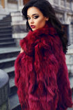 Beautiful girl with dark hair wearing  fashion red fur coat Stock Photo