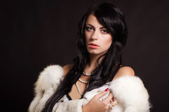 Beautiful girl with dark hair in a white fur coat Stock Photography
