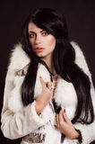 Beautiful girl with dark hair in a white fur coat Royalty Free Stock Photos