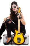 Beautiful girl in dark leather clothes holding an electric guitar Royalty Free Stock Photo