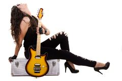 Beautiful girl in dark leather clothes holding an electric guitar Stock Images