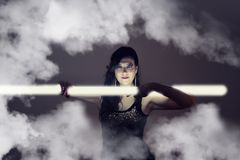 Beautiful girl in dark leather clothes holding a light tube Royalty Free Stock Photos