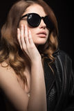 Beautiful girl in dark sunglasses, with curls and evening makeup. Beauty face. Picture taken in the studio on a black background royalty free stock photos