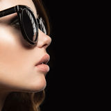 Beautiful girl in dark sunglasses, with curls and evening makeup. Beauty face. Picture taken in the studio on a black background royalty free stock photo