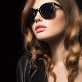 Beautiful girl in dark sunglasses, with curls and evening makeup. Beauty face. Royalty Free Stock Photography