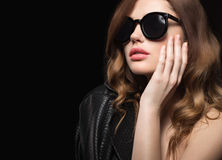 Beautiful girl in dark sunglasses, with curls and evening makeup. Beauty face. Picture taken in the studio on a black background stock images