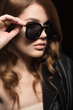 Beautiful girl in dark sunglasses, with curls and evening makeup. Beauty face. Picture taken in the studio on a black background royalty free stock photography