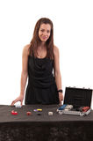 Beautiful girl dealer behind a table for game in poker on white royalty free stock images