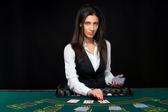 The beautiful girl, dealer, behind a table for poker Royalty Free Stock Images