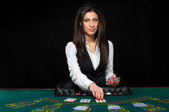 The beautiful girl, dealer, behind a table for poker stock images