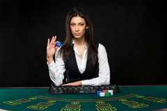 The beautiful girl, dealer, behind a table for poker Royalty Free Stock Photos