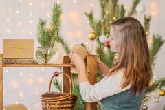 Beautiful girl decorate the room for Christmas stock images
