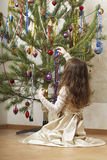 Beautiful girl decorates the Christmas tree. Stock Photography
