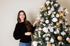 Beautiful girl decorates the Christmas tree.  Royalty Free Stock Photos