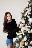Beautiful girl decorates the Christmas tree.  Royalty Free Stock Photo