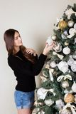 Beautiful girl decorates the Christmas tree.  Royalty Free Stock Image