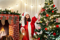Beautiful girl decorates the Christmas tree in santa hat, santa Royalty Free Stock Images