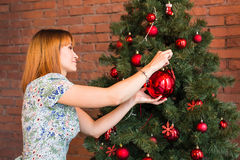 Beautiful girl decorating the Christmas tree Stock Photography
