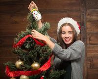 Beautiful girl decorating New Year tree at home Stock Image