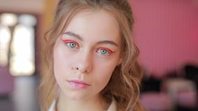 Beautiful girl demonstrate her bright spring makeup. She turn face and look at camera stock footage