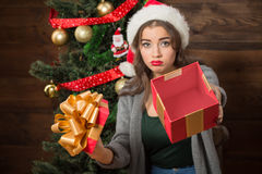 Beautiful girl demonstrating empty box of present near New Year tree Stock Photo